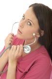 Porträt einer schönen professionellen ernsten jungen Ärztin Putting On ein Stethoskop Stockfotos
