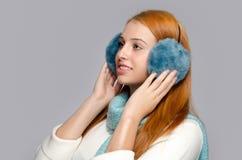 Porträt einer schönen roten Haarfrau, die blaue Ohrmuffen trägt Stockfotografie