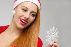 Porträt einer schönen roten Haarfrau, die eine Schneeflocke hält und betrachtet Lizenzfreie Stockfotografie