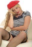 Porträt einer schönen sexy jungen französischen Frau, die ein rotes Barett-und Fisch-Nettostrümpfe trägt Lizenzfreie Stockfotografie