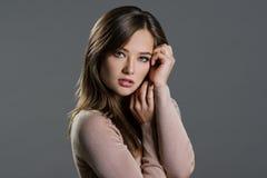 Porträt einer Schönheit auf einem grauen Hintergrund Lizenzfreie Stockfotografie