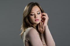 Porträt einer Schönheit auf einem grauen Hintergrund Stockfotografie