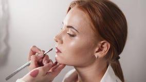 Porträt einer Schönheit, an der Lippenstift auf die Lippen im Studio zugetroffen wird stock video