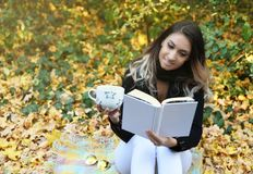 Porträt einer Schönheit, die ein Buch in einem Park mit einem Lächeln liest stockfotografie