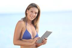 Porträt einer Schönheit, die ihre Tablette auf dem Strand verwendet Stockfoto