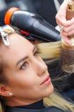 Porträt einer Schönheit in einem Friseursalon und des Friseurs, der blondes Haar mit Haartrockner und Rundbürste in a trocknet Stockbilder