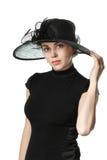 Porträt einer Schönheit in einem schwarzen Kleid und in einem Hut lokalisiert lizenzfreie stockbilder