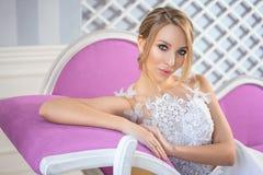 Porträt einer Schönheit in einem weißen Heiratskleid mit einem schönen Make-up und im Haar auf der Couch lizenzfreie stockbilder