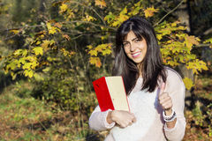 Porträt einer Schönheit im Herbstpark, ein Buch halten Stockbild