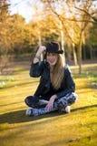 Porträt einer Schönheit im Hut auf dem Park, der auf sitzt lizenzfreies stockbild