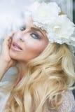 Porträt einer Schönheit mit dem langen blonden Haar und den grünen Augen, das hinter dem Glasfenster sitzt und flirtatiously läch Lizenzfreie Stockbilder