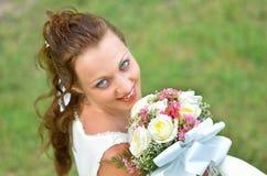 Porträt einer Schönheit mit einem Blumenstrauß von Blumen auf einem BAC Lizenzfreies Stockbild