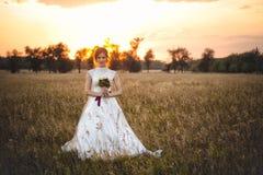 Porträt einer schicken Braut in einem Hochzeitskleid, das bei Sonnenuntergang auf dem Gebiet steht stockfoto