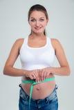 Porträt einer schwangeren Frau mit Maßband Stockfoto