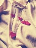Porträt einer silbernen Halskette mit roten Herzen auf einem Blatt stockfotografie