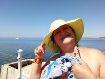 Porträt einer sonnenverbrannten Frau, die auf einem Pier steht Lizenzfreie Stockbilder