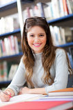 Studentin in einer Bibliothek Stockbild