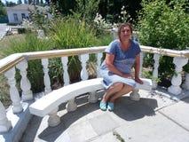 Porträt einer suntanned Frau, die auf einer Bank sitzt Stockfotografie