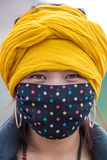 Porträt einer tibetanischen Frau, die eine Maske trägt Lizenzfreies Stockbild