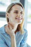 Porträt einer träumerischen jungen Frau, die ihren Hals berührt Stockbild