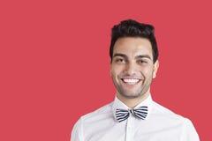 Porträt einer tragenden Fliege des glücklichen mittleren erwachsenen Mannes über rotem Hintergrund Stockfoto