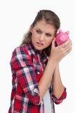 Porträt einer traurigen Frau, die eine piggy Bank rüttelt Lizenzfreies Stockfoto
