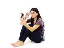 Porträt einer verärgerten Frau mit der geballten Faust, die ihr Mobiltelefon betrachtet Lizenzfreie Stockbilder