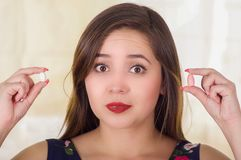 Porträt einer verwirrten Frau, die in hält, übergibt einer weichen Gelatine vaginale Tablette oder Zäpfchen, Behandlung von Krank Lizenzfreie Stockbilder