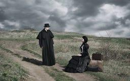 Porträt einer victorian Dame im schwarzen Sitzen auf der Straße mit ihrem Gepäck und Herrn, die in der Nähe stehen stockfotografie