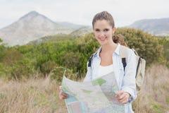 Porträt einer wandernden jungen Frau, die Karte hält Stockfoto