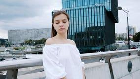 Porträt einer wunderschönen jungen Geschäftsfrau, die auf der Stadtbrücke auf der Straße steht, modernes blaues Glasbüro stock video footage