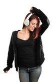 Porträt einer zufällig gekleideten hörenden Musik des jungen Mädchens Lizenzfreies Stockfoto