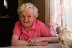 Porträt eines älteren Frauenpensionärs, der an einem Tisch in der Küche in seinem Haus sitzt stockbild