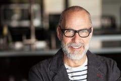 Porträt eines älteren Mannes, der an der Kamera lächelt lizenzfreies stockfoto