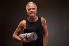 Porträt eines älteren Mannes mit einer Yogamatte Stockbilder