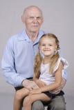 Porträt eines älteren Mannes mit Enkelin Stockbild