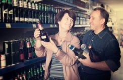 Porträt eines älteren Paares, das im Supermarkt ein Bier kauft lizenzfreies stockfoto