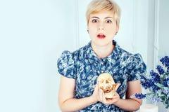 Porträt eines überraschenden schönen blonden Mädchens, das Schädel hält Stockfotografie
