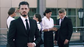 Porträt eines überzeugten Geschäftsmannes, der vor seinen Mitarbeitern steht stock video