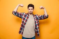 Porträt eines überzeugten jungen Mannes, der Muskeln biegt Lizenzfreies Stockfoto