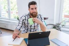Porträt eines überzeugten selbstständigen jungen Mannes, der am Schreibtisch sitzt lizenzfreie stockfotografie