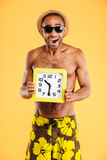 Porträt eines afrikanischen Mannes in der Badebekleidung, die Wanduhr hält Stockbilder