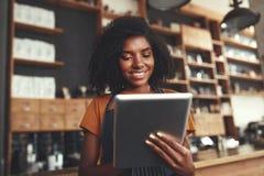 Porträt eines afrikanischen weiblichen Caféinhabers, der digitale Tablette verwendet stockfoto