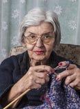 Porträt eines alte Frauen-Strickens stockfotos
