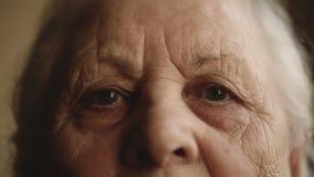 Porträt eines alten einsamen Menschen, der heraus das Fenster schaut stock footage