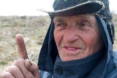 Porträt eines alten Mannes in unordentliche Kleidung und Hut, die seinen Zeigefinger anhoben, habe ich eine Idee stockbilder