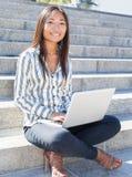 Porträt eines asiatischen Mädchens, das einen Laptop im Freien verwendet Lizenzfreie Stockfotos