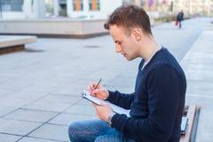 Porträt eines attraktiven Jugendlichjungen, der auf einer Holzbank sitzt Stockfotografie