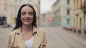 Porträt eines attraktiven jungen kaukasischen Mädchens, das Beige trägt, Lächeln und Laugen im Hintergrund der Stadt stock footage