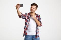 Porträt eines attraktiven jungen Mannes, der ein selfie nimmt Stockbilder
